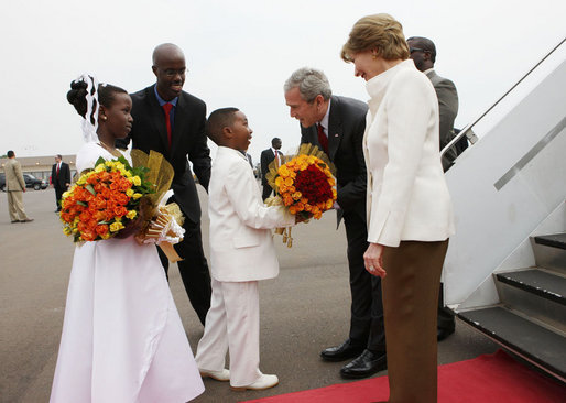 President George W. Bush and Mrs. Laura Bush are greeted by children with flowers on their arrival Tuesday, Feb. 19, 2008 to Kigali International Airport in Kigali, Rwanda. White House photo by Eric Draper