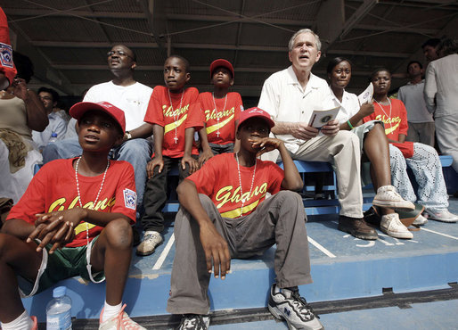 President George W. Bush sits in the stands and watches a tee ball game Wednesday, Feb. 20, 2008, at the Ghana International School in Accra, Ghana. White House photo by Eric Draper