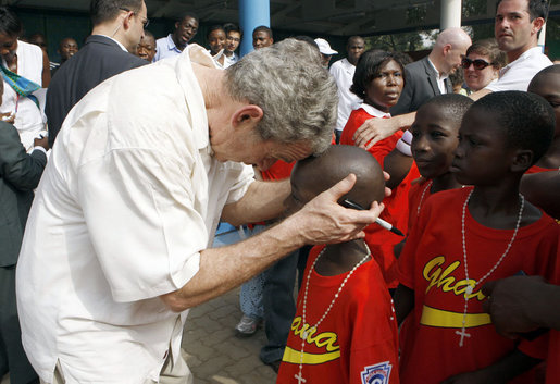 President George W. Bush embraces a young boy after a tee ball game Wednesday, Feb. 20, 2008, at the Ghana International School in Accra, Ghana. White House photo by Eric Draper