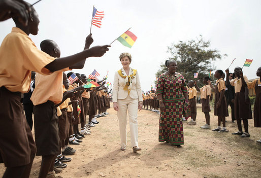 Mrs. Laura Bush and Ghana first lady Mrs. Theresa Kufuor, are greeted by singing students waving flags, on their arrival to Mallam D/A Primary School, Wednesday, Feb. 20, 2008 in Accra, Ghana. White House photo by Shealah Craighead