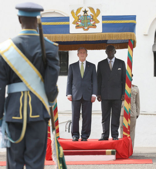 President George W. Bush stands with Ghana President John Agyekum Kufuor during the official welcome to Osu Castle, Wednesday, Feb. 20, 2008 in Accra, Ghana. White House photo by Eric Draper