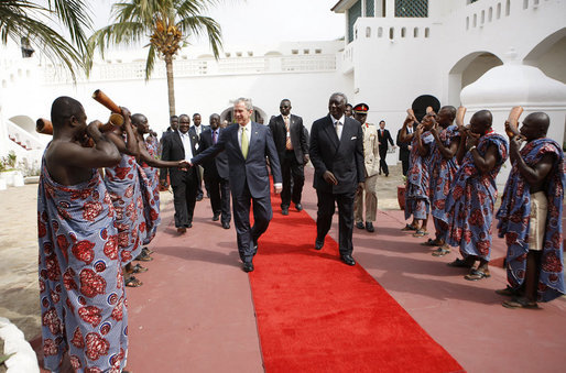 President George W. Bush, walking with Ghana President John Agyekum Kufuor, reaches out to shake hands with a ceremonial greeter on his arrival to Osu Castle, Wednesday, Feb. 20, 2008 in Accra, Ghana. White House photo by Eric Draper