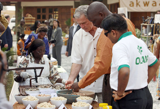 President George W. Bush looks over a table of local food items Wednesday, Feb. 20, 2008, during his visit to the International Trade Fair Center in Accra, Ghana. White House photo by Eric Draper