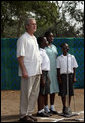 President George W. Bush stands at home plate with 3 members of the Ghana International School choir as they sing the Ghanaian National Anthem Wednesday, Feb. 20, 2008, at a tee ball game at the Ghana International School in Accra, Ghana. White House photo by Eric Draper