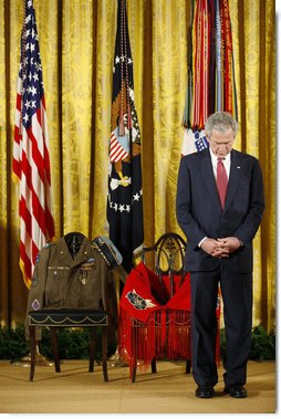 President George W. Bush bows his head during a prayer Monday, March 3, 2008 in the East Room of the White House, standing before two chairs in honor of U.S. Army Master Sgt. Woodrow Wilson Keeble, left, and his wife, Bloosom, moments before presenting members of the Keeble family with the Medal of Honor, posthumously, in honor of Master Sgt. Keeble's gallantry during his service in the Korean War. Keeble is the first full-blooded Sioux Indian to receive the Medal of Honor. White House photo by Eric Draper