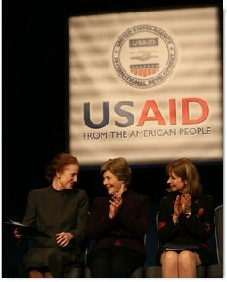 Mrs. Laura Bush applauds as she's joined on stage by Ms. Henrietta Fore, left, Administrator of the U.S. Agency for International Development and Director of the United States Foreign Assistance, and Ambassador Paul Dobriansky, Under Secretary of State for Democracy and Global Affairs, for the USAID Celebration of International Women's Day Friday, March 7, 2008, at the Ronald Reagan Building in Washington, D.C. White House photo by Joyce N. Boghosian
