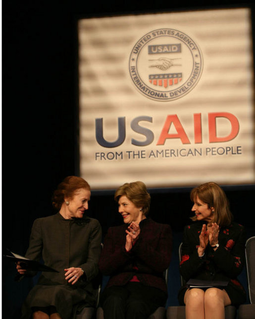 Mrs. Laura Bush applauds as she's joined on stage by Ms. Henrietta Fore, left, Administrator of the U.S. Agency for International Development and Director of the United States Foreign Assistance, and Ambassador Paula Dobriansky, Under Secretary of State for Democracy and Global Affairs, for the USAID Celebration of International Women's Day Friday, March 7, 2008, at the Ronald Reagan Building in Washington, D.C. White House photo by Joyce N. Boghosian