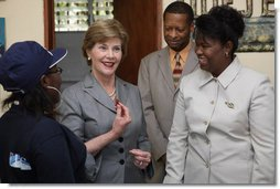 "Mrs. Laura Bush, joined by Guerda Previlon, right, chief of party IDEJEN, and Gabriel Bienime, Haiti Education Minister, visits with a student enrolled in the IDEJEN educational program at the College de St. Martin Tours Thursday, March 13, 2008, in Port-au-Prince, Haiti. In an address to the faculty and staff Mrs. Bush said, ""Educating its young people is one of the best things a country can do to ensure its continued development.""  White House photo by Shealah Craighead"