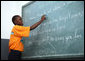 A student at the IDEJEN educational program reads from a chalkboard Thursday March, 13, 2008, during Mrs. Laura Bush's visit to the program at the College de St. Martin Tours in Port-au-Prince, Haiti. White House photo by Shealah Craighead