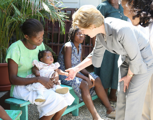 Mrs. Laura Bush is introduced to a participant and her infant daughter at the GHESKIO HIV/AIDS Center's women's clinic, Thursday, March 13, 2008, in Port-au-Prince, Haiti. The program was initiated to help improve the lives of HIV patients. White House photo by Shealah Craighead