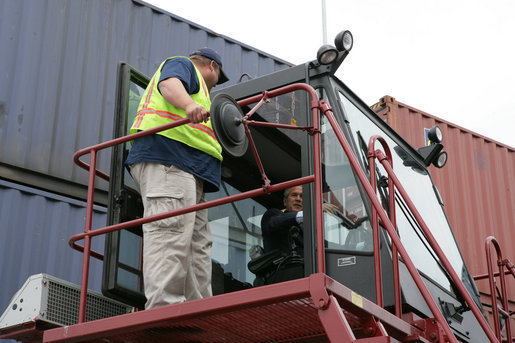 President George W. Bush sits inside the cab of a stacker as its operator, Frederick Bishop, looks on Tuesday, March 18, 2008, during a tour of Coastal Maritime Stevedoring, LLC at the Blount Island Marine Terminal in Jacksonville, Fla. White House photo by Chris Greenberg