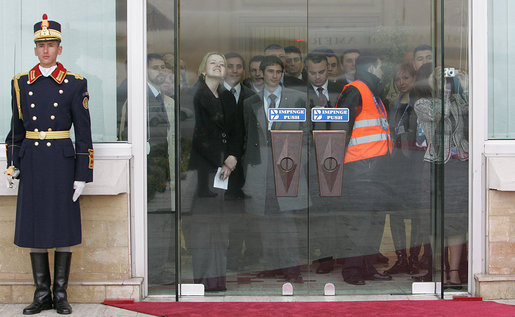 A crowd gathers inside the doors to watch as President George W. Bush and Mrs. Laura Bush arrive at the Henri Coanda International Airport Tuesday, April 1, 2008, in Bucharest, Romania. White House photo by Chris Greenberg