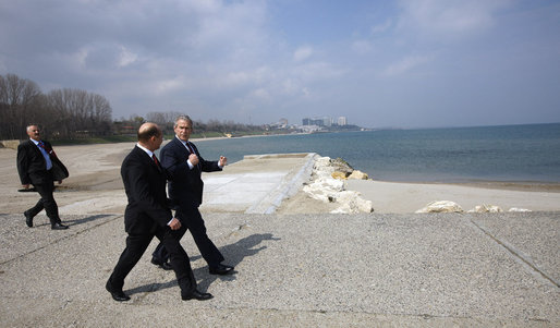 With the Black Sea behind them, President George W. Bush and President Taian Basescu walk along a pier Wednesday, April 2, 2008, during a tour of the Romanian leader's presidential retreat in Neptun, Romania. White House photo by Eric Draper