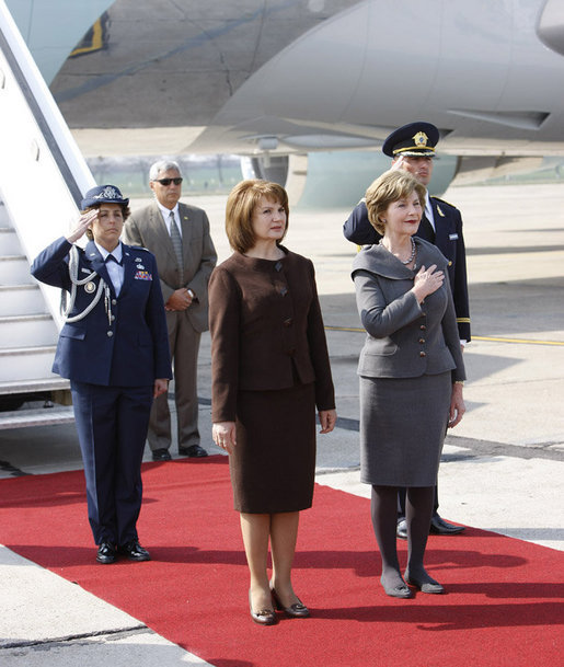 Mrs. Laura Bush holds her hand over her heart during the playing of the national anthem Wednesday, April 2, 2008, as she stands with Mrs. Maria Basescu, spouse of Romania's President Traian Basescu, on the red carpet during the arrival ceremony at Mihail Kogalniceanu Airport in Constanta, Romania. White House photo by Eric Draper