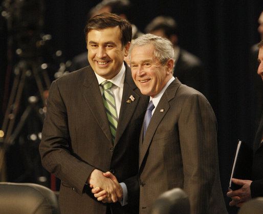 President George W. Bush and President Mikheil Saakashvili of Georgia, shake hands as they smile at cameras before the start of the afternoon session of the 2008 NATO Summit in Bucharest. White House photo by Eric Draper