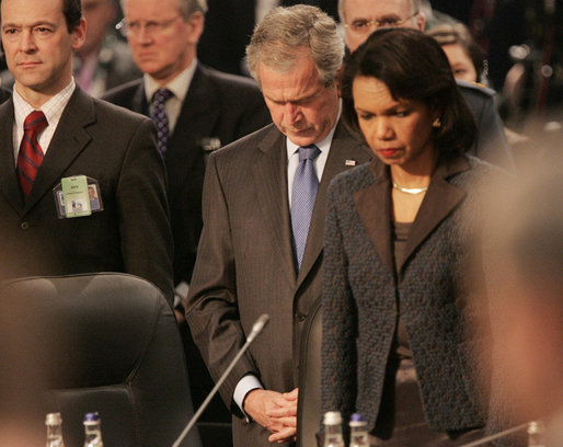 President George W. Bush bows his head as he stands with Secretary of State Condoleezza Rice Thursday, April 3, 2008, at the start of the North Atlantic Council Summit in Bucharest. White House photo by Chris Greenberg