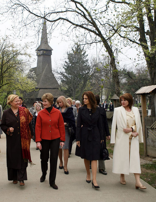 Mrs. Laura Bush walks with the spouses of NATO leaders Thursday, April 3, 2008, at the open-aired Dimitrie Gusti Village Museum in Bucharest. With her are Maria Basescu, right, spouse of Romania's President Traian Basescu, and Alexandra Coman, fiancé of Romania's Foreign Minister Adrian Cioroianu. White House photo by Shealah Craighead