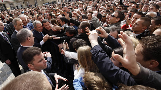 President George W. Bush reaches out to the crowd Saturday during his visit to St. Mark's Square in Zagreb. More than 3000 people were on hand to welcome the President during his visit. White House photo by Eric Draper