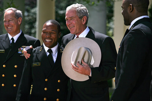 President George W. Bush is presented a cowboy hat and a Commander-in-Chief Trophy ring by Co-Captains Reggie Campbell, left, and Irv Spencer Monday, April 14, 2008, during the presentation of the Commander-in-Chief's Trophy to the United States Naval Academy Football Team in the Rose Garden at the White House. White House photo by Noah Rabinowitz