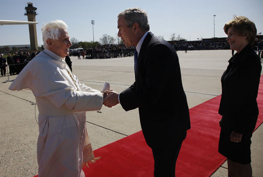 President George W. Bush takes the hand of Pope Benedict XVI as he and Mrs. Laura Bush welcomed the Pope to the United States upon his landing at Andrews Air Force Base, Maryland. Pope Benedict will visit the White House Wednesday and celebrate Mass Thursday before continuing on to New York City. White House photo by Eric Draper
