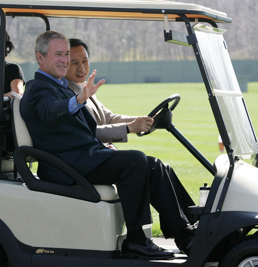 President George W. Bush waves as South Korean President Lee Myung-bak drives their golf cart Friday, April 18, 2008, at the Presidential retreat at Camp David, Md. White House photo by Joyce N. Boghosian