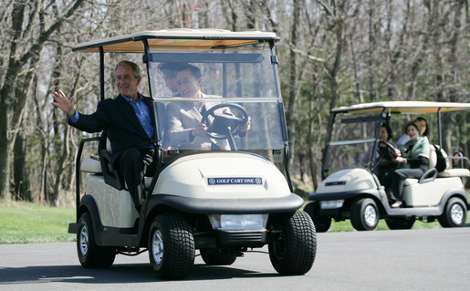President George W. Bush waves as South Korean President Lee Myung-bak drives their golf cart, followed by Laura Bush and South Korea first lady Kim Yoon-ok in theirs Friday, April 18, 2008, at the Presidential retreat at Camp David, Md. White House photo by Shealah Craighead