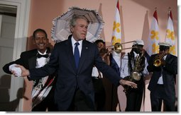 President George W. Bush steps on stage at the U.S. Chamber of Commerce reception to join members of the Euphonic Jazz Band Monday evening, April 21, 2008, prior to attending the 2008 North American Leaders' Summit dinner in New Orleans. White House photo by Joyce N. Boghosian