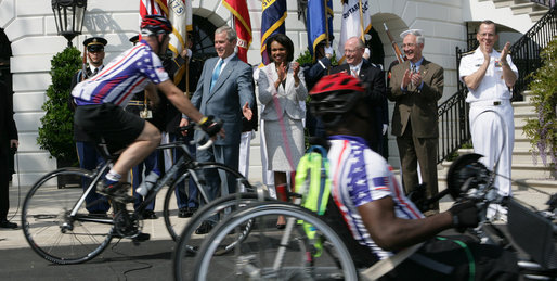President George W. Bush reaches out to participants of the Wounded Warriors Soldier Ride as they cross in front of him during the kickoff Thursday of the White House to Lighthouse ride. White House photo by Chris Greenberg