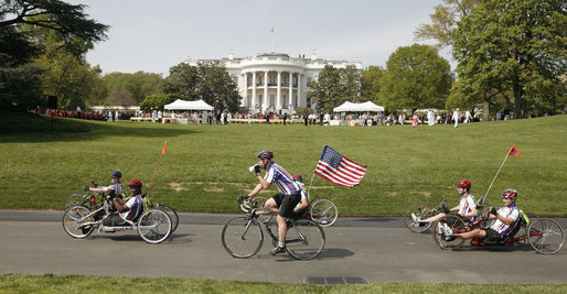 "Members of the Wounded Warrior Project's Soldier Ride head around the South Lawn of the White House Thursday, April 24, 2008, during the kickoff of the annual ""Soldier Ride: White House to Lighthouse Challenge"" bike ride. White House photo by Joyce N. Boghosian"