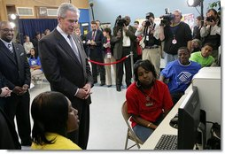 President George W. Bush looks over the shoulders of middle school students as they work on projects for Malaria Awareness Day Friday, April 25, 2008, during his visit to the Northwest Boys & Girls Club in Hartford, Conn. White House photo by Chris Greenberg