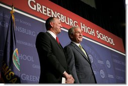 President George W. Bush stands next to Greensburg Schools Superintendent Darin Headrick before making remarks during commencement ceremonies for the Greensburg High School graduating class of 2008. The town of Greensburg, KS was almost entirely destroyed when a tornado tore through the town one year ago today. White House photo by Chris Greenberg