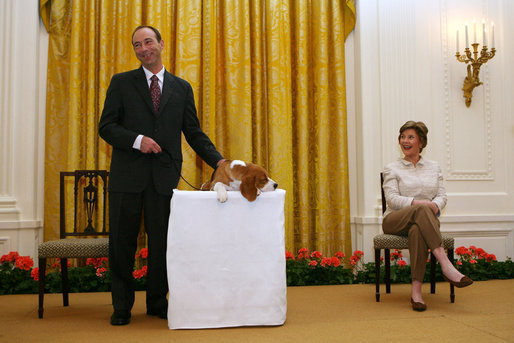 Mrs. Laura Bush looks on as the Westminster Kennel Club's 2008 Best in Show Winner, Uno, and his co-owner Eddie Dziuk address guests during their visit to the White House Monday, May 5, 2008, in the East Room of the White House. White House photo by Shealah Craighead