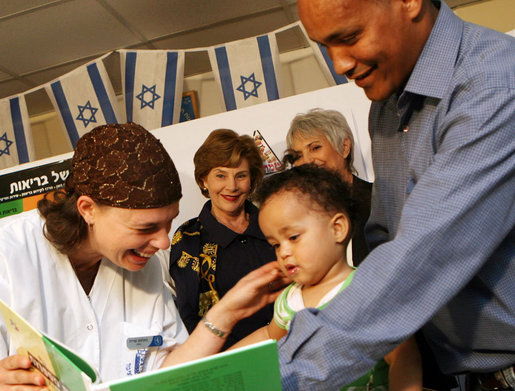 Mrs. Laura Bush looks on during an examination of 1-year-old Orie Holkan during a visit Wednesday, May 14, 2008, to the Tipat Chalav-Gonenim Neighborhood Mother and Child Care Center in Jerusalem. With them are Ms. Sarit Fuast, the nurse, and Talala Holkan, the young child's father. White House photo by Shealah Craighead