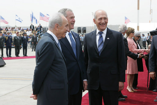President George W. Bush shares a smile with Israel's President Shimon Peres, left, and Prime Minister Ehud Olmert, as arrival ceremonies wind down Wednesday, May 14, 2008, at Ben Gurion International Airport for the U.S. leader and Mrs. Laura Bush. White House photo by Joyce N. Boghosian