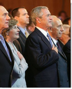 President George W. Bush and Laura Bush are seen with Israeli leaders Prime Minister Ehud Olmert, left, and Israeli President Shimon Peres during the playing of the National Anthem Wednesday, May 14, 2008 in Jerusalem, during a celebration of Israel's 60th anniversary as a nation at the Israeli Presidential Conference 2008 at the Jerusalem International Convention Center. White House photo by Shealah Craighead