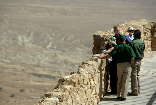 President George W. Bush and Mrs. Laura Bush and Prime Minister Ehud Olmert of Israel and Mrs. Aliza Olmert stand on the upper level of Masada, a palatial fortress built by King Herod, and listen to Eitan Campbell, Director of Masada National Park during their visit to the historic site Thursday, May 15, 2008. On the fringe of the Judean Desert near the shore of the Dead Sea, the camps, fortifications and assault ramp at its base constitute the most complete surviving ancient Roman siege system in the world. White House photo by Shealah Craighead