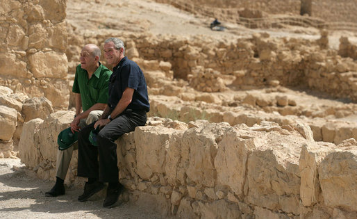 President George W. Bush and Prime Minister Ehud Olmert sit on a wall as they take a break from their tour of Masada Thursday, May 15, 2008. The President and Mrs. Laura Bush took the opportunity to visit the historic site during their two-day visit to Israel to help celebrate the 60 anniversary of the country's independence. White House photo by Shealah Craighead