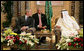 President George W. Bush smiles as he and King Abdullah bin Abdulaziz exchange greetings during a arrival ceremony Friday, May 16, 2008, at the Riyadh-King Khaled International Airport in Riyadh. At center is interpreter Gamal Helal. White House photo by Chris Greenberg