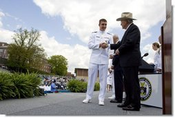 "Vice President Dick Cheney presents commission papers to a U.S. Coast Guard Academy graduate, Wednesday, May 21, 2008, during commencement exercises in New London, Conn. During his address to the graduates the Vice President said, ""This branch of the armed forces has given steady service to the United States of America since the year 1790 -- and in that time the Coast Guard has saved more than a million lives."" He added, ""As you step forward to accept new duties, your fellow citizens look up to you for the oath you take, the traditions you uphold, and the standards you live by."" White House photo by David Bohrer"