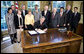 President George W. Bush signs H.R. 493, the Genetic Information Nondiscrimination Act of 2008, Wednesday, May 21, 2008, in the Oval Office. The Genetic Information Nondiscrimination Act would prevent health insurers from canceling, denying, refusing to renew, or changing the terms or premiums of coverage based solely on a genetic predisposition toward a specific disease. The legislation also bars employers from using individuals' genetic information when making hiring, firing, promotion, and other employment-related decisions. White House photo by Eric Draper