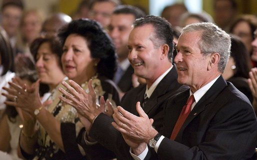 President George W. Bush applauds the entertainment of vocalist Willy Chirino during a Day of Solidarity with the Cuban People Wednesday, May 21, 2008, in the East Room of the White House. Seated next to him are Miguel Sigler Amaya, a former political prisoner, and his wife, Josefa Lopez Pena. White House photo by Joyce N. Boghosian