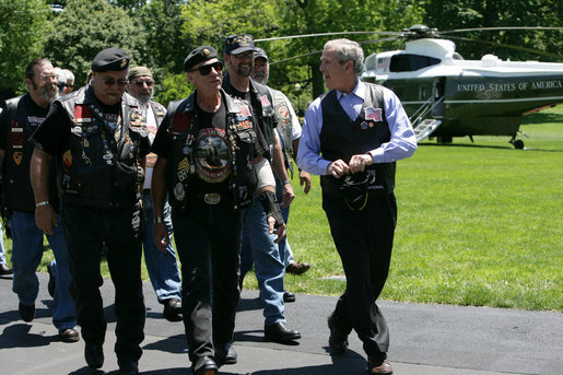 President George W. Bush shares a laugh with National Executive Director of Rolling Thunder Artie Muller as he escorts a group of the motorcyle riders to the Oval Office. White House photo by Chris Greenberg