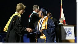 "Mrs. Laura Bush congratulates a graduate during commencement exercises Thursday, May 29, 2008, at Enterprise High School in Enterprise, Alabama. Mrs. Bush was on hand to deliver the commencement address, and she told the class -- that lost four of its members in deadly tornadoes last year -- and told the Class of 2008, ""As you graduate tonight, take with you memories of your teachers' and classmates' support after the storm, the blue and white worn by students at rival schools, and the donations that came pouring in from around the country."" White House photo by Shealah Craighead"