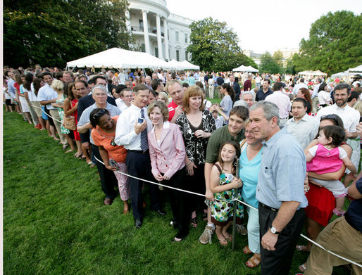 President George W. Bush poses for photos with some of the hundreds of guests attending the annual Congressional Picnic on the South Lawn of the White House, Thursday evening, June 5, 2008, for members of Congress and their families. White House photo by Chris Greenberg