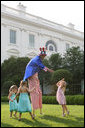 Uncle Sam on stilts reaches out to slap high-five with children at the annual Congressional Picnic on the South Lawn of the White House, Thursday evening, June 5, 2008. White House photo by Grant Miller