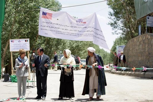 Mrs. Laura Bush, left, assists local officials with the ribbon cutting ceremony June 9, 2008 in Afghanistan at the ground-breaking ceremonies for the 1.96 kilometer Bamiyan road project through the bazaar. The new road will link up with a 1.72 kilometer road from the airport to the town center completed in 2007 with U.S. support. White House photo by Shealah Craighead