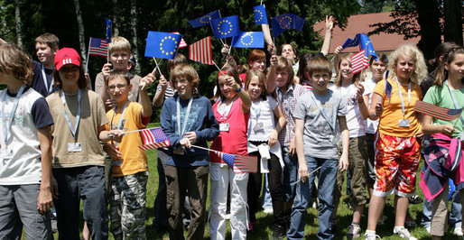 Young children wave American and European Union flags as they wait for President George W. Bush as he participates in a United States - European Union Working Lunch Tuesday, June 10, 2008, at the Brdo Congress Center in Kranj, Slovenia. White House photo by Chris Greenberg