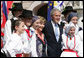 President George W. Bush and Laura Bush pose for a photo with children dressed in traditional outfits during their visit Tuesday, June 10, 2008, to the Lipizzaner Horse Exhibition at Brdo Castle in Kranj, Slovenia. White House photo by Shealah Craighead