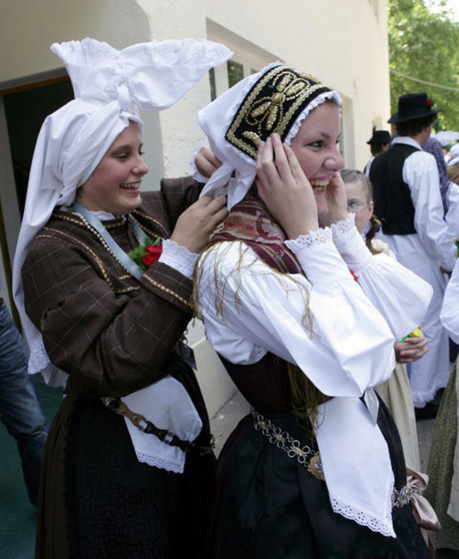 A girl helps her friend tie her head scarf as they wait for President George W. Bush's as he participates in a United States - European Union Working Lunch Tuesday, June 10, 2008, at the Brdo Congress Centre in Kranj, Slovenia. White House photo by Chris Greenberg