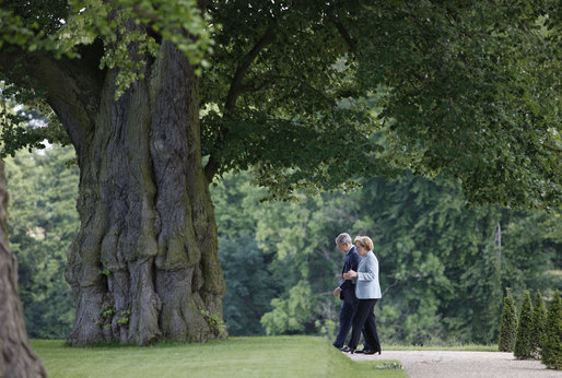 President George W. Bush walks with Germany's Chancellor Angela Merkel on the grounds of the Schloss Meseberg Wednesday, June 11, 2008, during the President's visit to Europe. The two spent the day in meetings and held a joint press availability before the President continued on to Rome. White House photo by Eric Draper